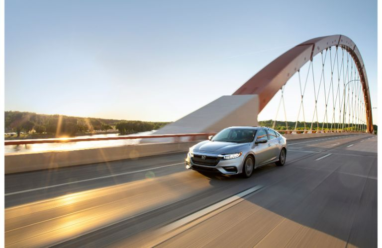 2020 Honda Insight exterior shot with silver paint color driving over a bridge as the background blurs