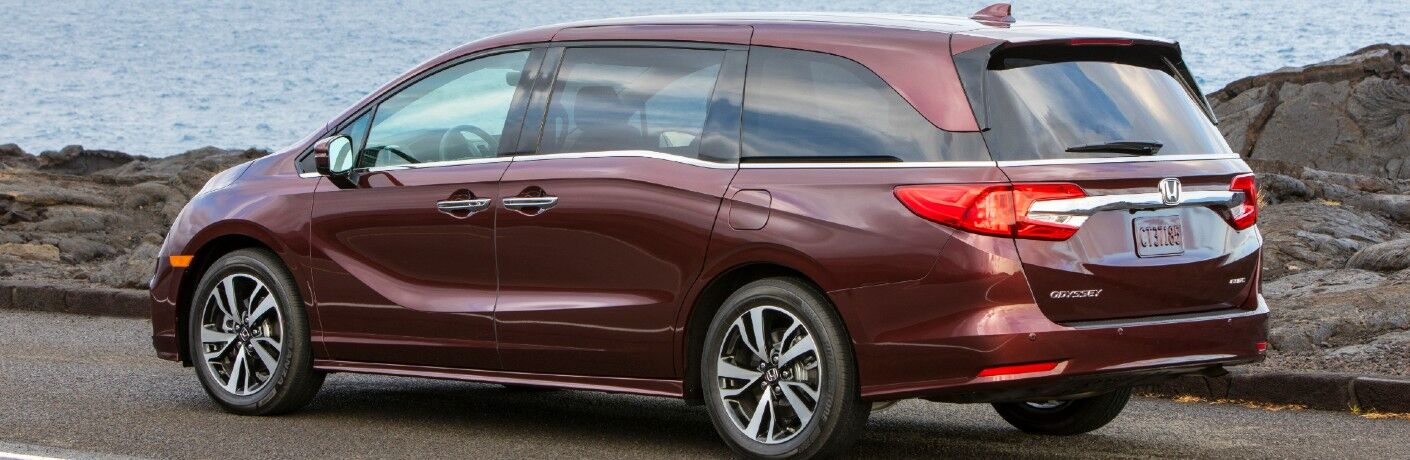 2020 Honda Odyssey exterior side rear shot with dark red paint color parked on the side of a road near a rocky beach and ocean waves