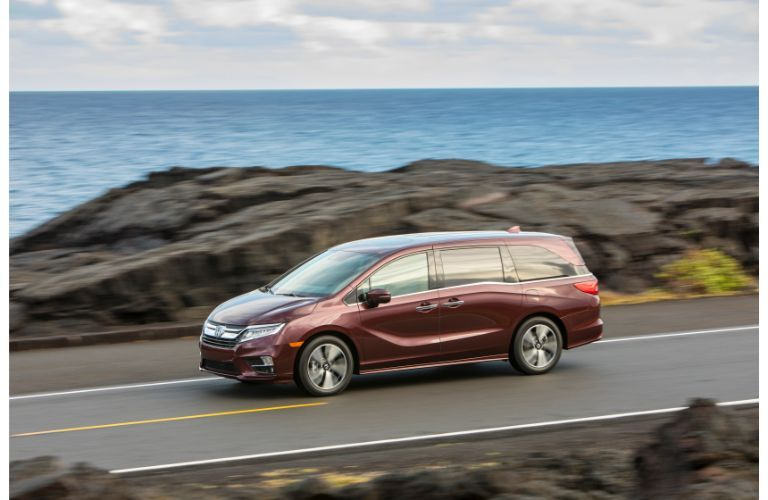 2020 Honda Odyssey exterior side shot with deep scarlet pearl paint color driving down a coastal highway