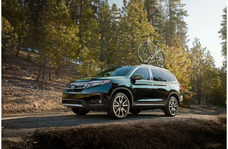2020 Honda Pilot Elite exterior shot parked on a forest road as trees loom overhead