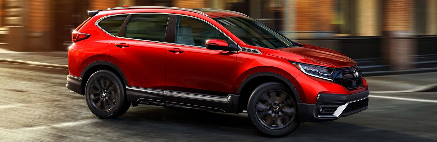 2021 Honda CR-V exterior shot with red paint color driving through an urban city at a crosswalk