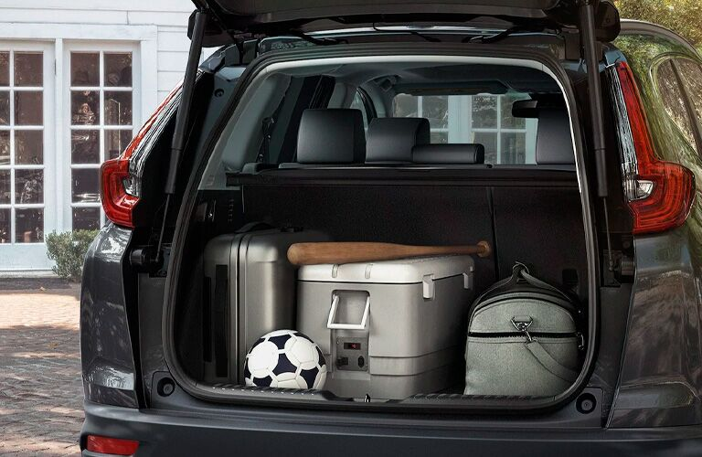 2021 Honda CR-V exterior rear shot of open trunk loaded with luggage, a soccer ball, and a baseball bat