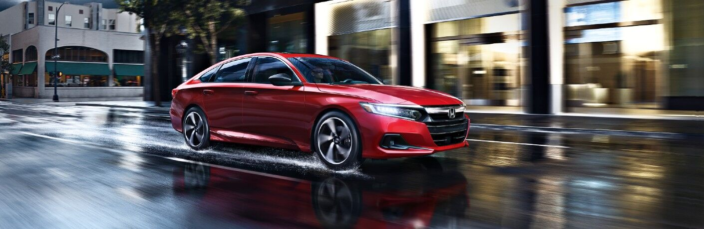 2021 Honda Accord Sport exterior shot with red paint color driving on wet roads in a city