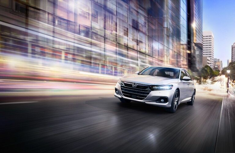 2021 Honda Accord Touring exterior shot with Platinum White Pearl paint color driving through a city at night as lights blur in the background