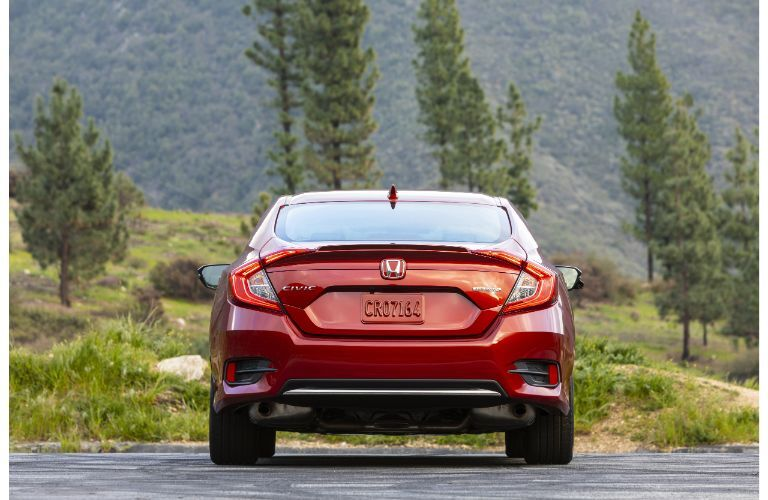 2021 Honda Civic Sedan Touring exterior rear shot with Molten Lava Pearl paint color parked on a forest road