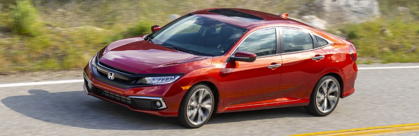 2021 Honda Civic Sedan Touring exterior shot with Molten Lava Pearl paint color driving on a country highway