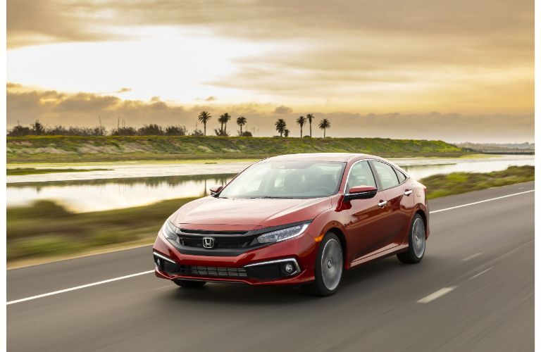 2021 Honda Civic Sedan Touring exterior shot with Molten Lava Pearl paint color driving past a marsh as the sun sets