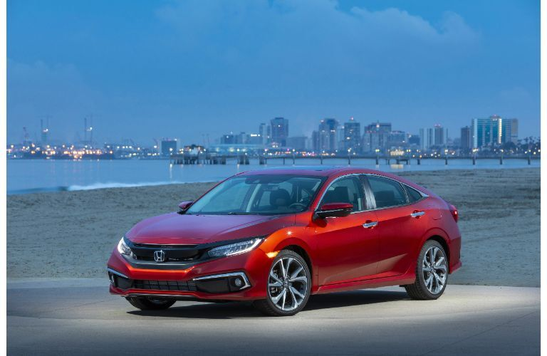 2021 Honda Civic Sedan Touring exterior shot with Molten Lava Pearl paint color parked near a beach at night