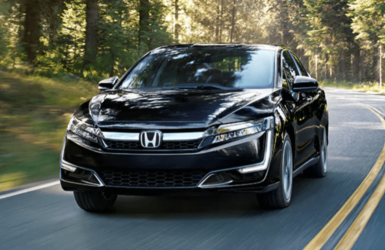 2021 Honda Clarity Plug-In Hybrid exterior shot with Crystal Black Pearl paint color driving through a forest highway