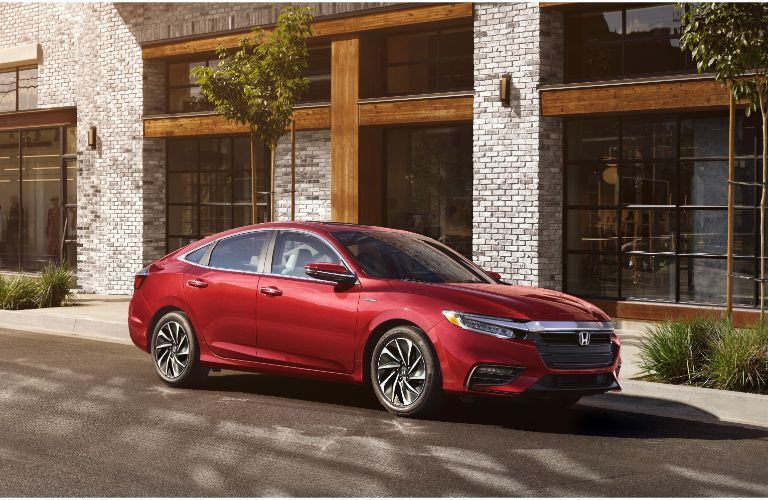 2021 Honda Insight exterior shot with Radiant Red Metallic paint color parked outside a fancy white and gray brick building
