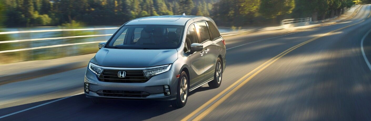2021 Honda Odyssey minivan model exterior shot in silver gray paint color driving on a country highway flanked by forest trees and lakes