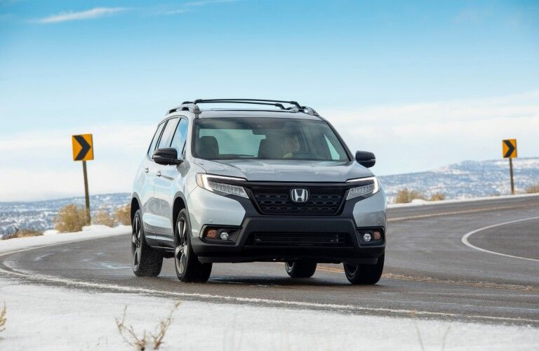 2021 Honda Passport exterior shot with silver metallic paint color driving on a snowy mountain highway road