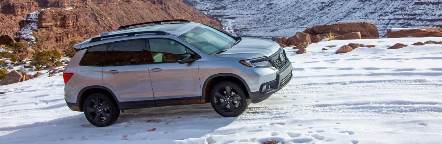 2021 Honda Passport exterior side overhead shot with silver metallic paint color driving on a snowy mountain road