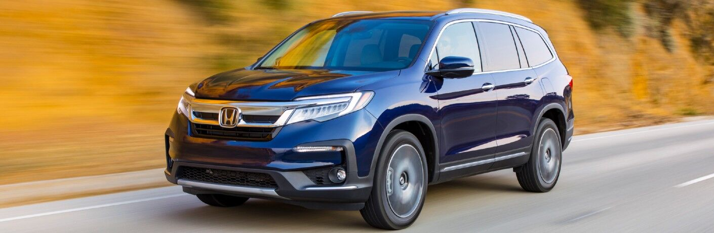2021 Honda Pilot Elite exterior with Obsidian Blue Pearl paint color driving on a forest mountain highway