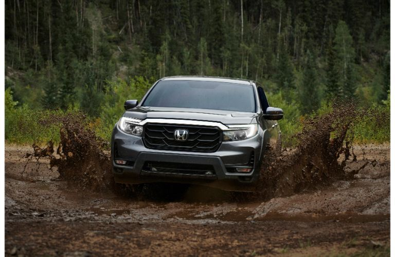 2021 Honda Ridgeline exterior front shot driving through mud as it splashes up with a forest background