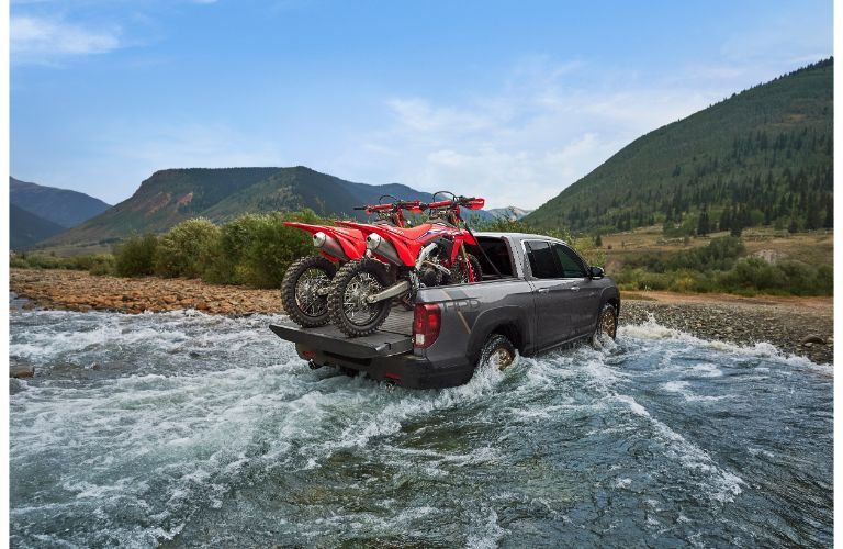 2021 Honda Ridgeline exterior rear shot with motorbikes in its bed driving out of water onto a beach of rocks and gravel