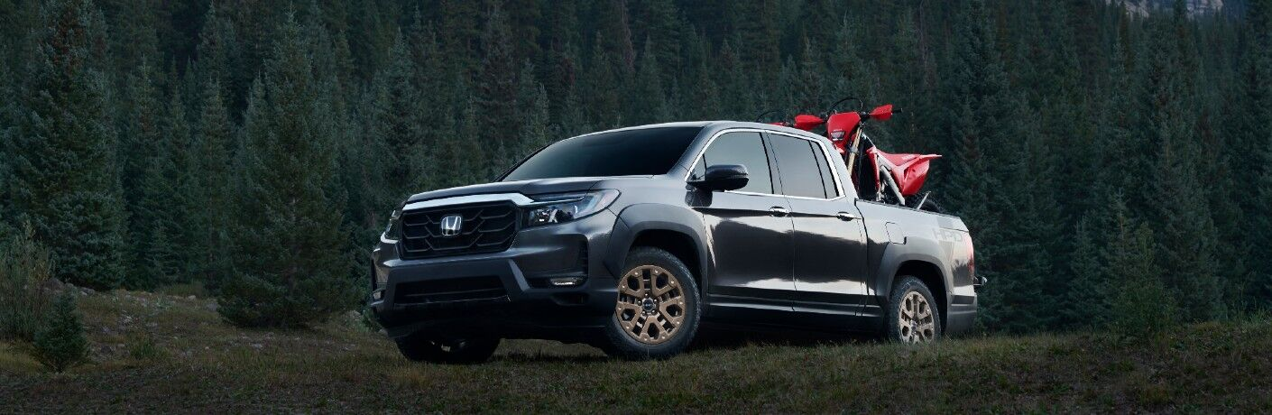 2021 Honda Ridgeline exterior shot with a motorcycle bike in its bed parked on grass with a pine tree forest background