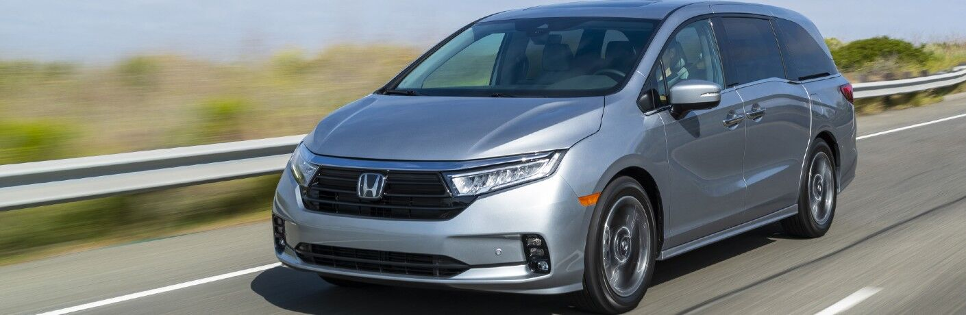 2022 Honda Odyssey exterior shot with Lunar Silver Metallic paint color driving down a country highway