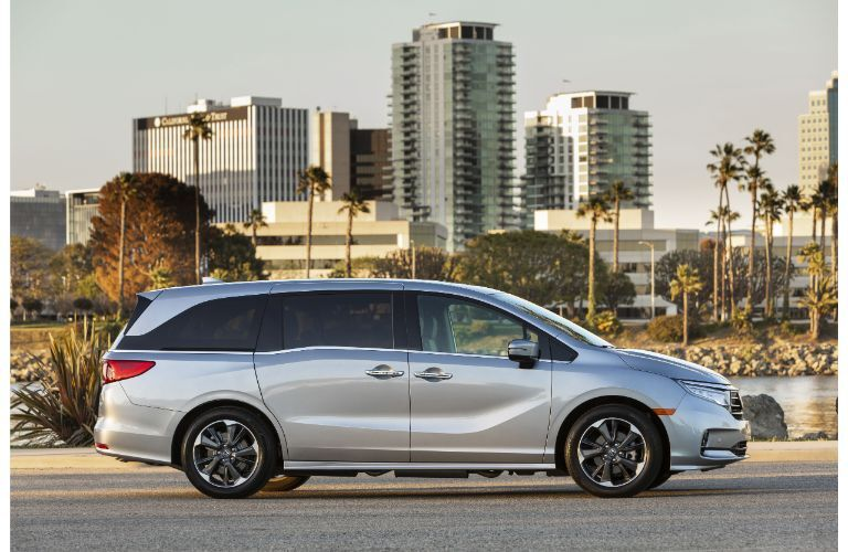 2022 Honda Odyssey exterior side shot parked on an asphalt plaza with a city skyline background