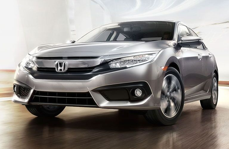 2018 Honda Civic Sedan driving up a bright ramp
