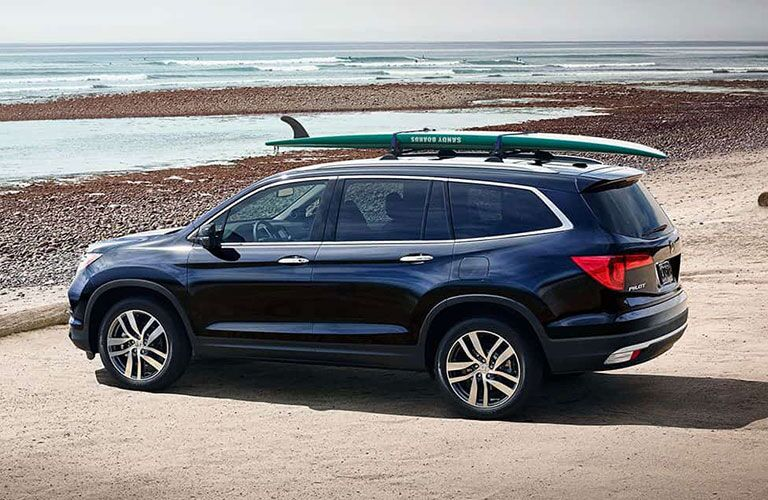2018 Honda Pilot parked at a beach with a surfboard on top