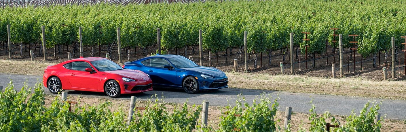 View of two 2018 Toyota 86 sports cars parked on a county road with crops in the background