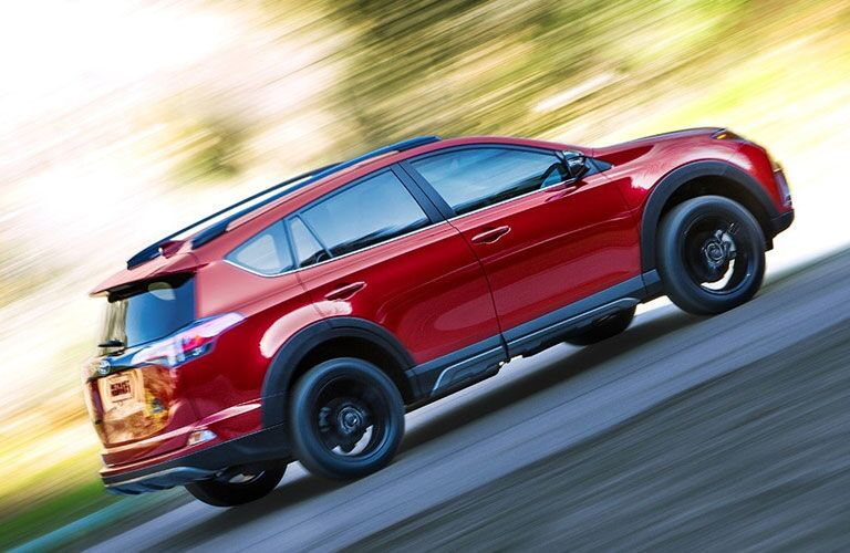 2018 Toyota RAV4 exterior shot with red paint color driving up a hill as the background blurs with speed