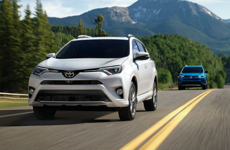 2018 Toyota RAV4 models, white and blue, driving outside on a forest road with a mountain behind them