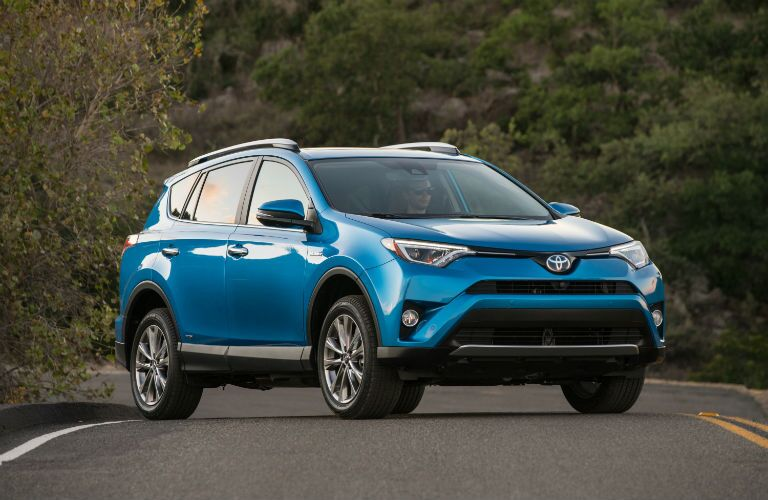 Exterior view of the front of a light blue 2018 Toyota RAV4 parked on a road surrounded by woods