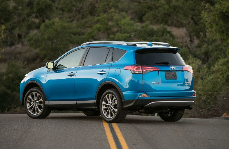 Exterior view of the rear of a light blue 2018 Toyota RAV4 parked in the middle of a road surrounded by woods