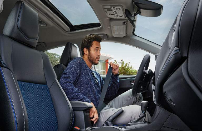 man buckling his seatbelt in 2018 Toyota Corolla