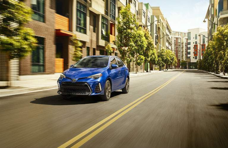 blue 2018 Toyota Corolla driving down the street