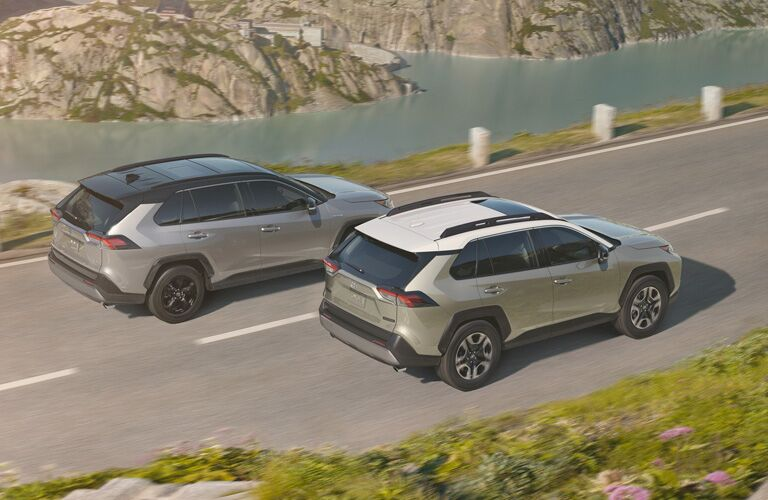 exterior overhead shot of two 2019 Toyota RAV4 models driving side by side down a highway