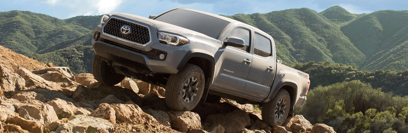 2019 Toyota Tacoma exterior shot with gray paint color driving up a rocky hill with grassy mountains in the background