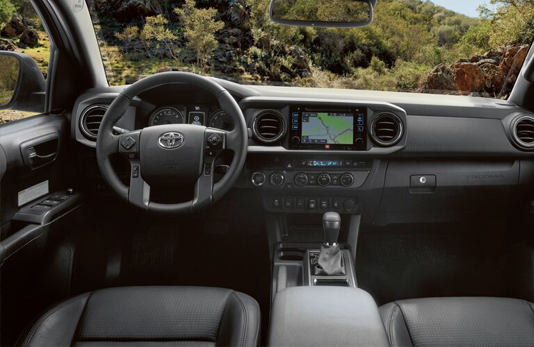 2019 Toyota Tacoma interior shot from driver's view of front seating, steering wheel, transmission knob, and dashboard layout with display screens