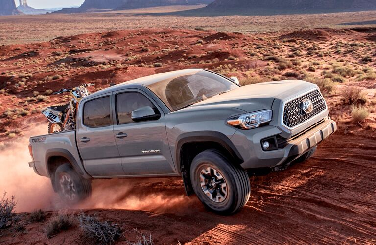 Exterior view of a gray 2019 Toyota Tacoma driving down a dirt road with a dirt bike in the bed