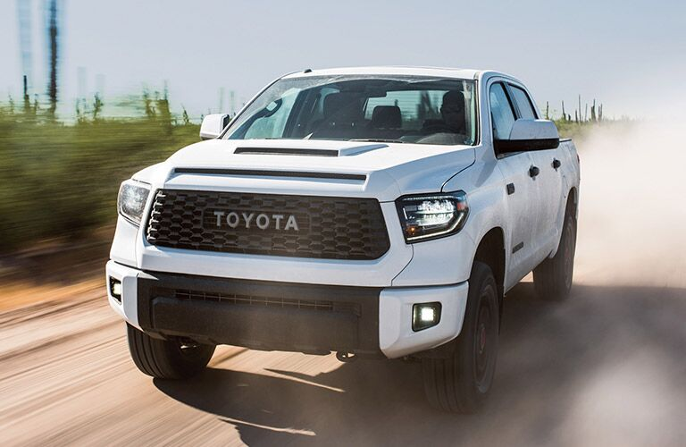 Exterior view of the front of a white 2019 Toyota Tundra driving down a dusty road