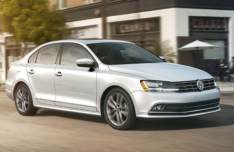White 2018 Volkswagen Jetta driving down the road in front of a restaurant
