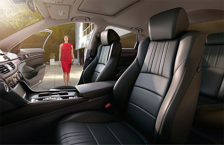 A woman in a red dress approaches the open door of a 2019 Honda Accord.