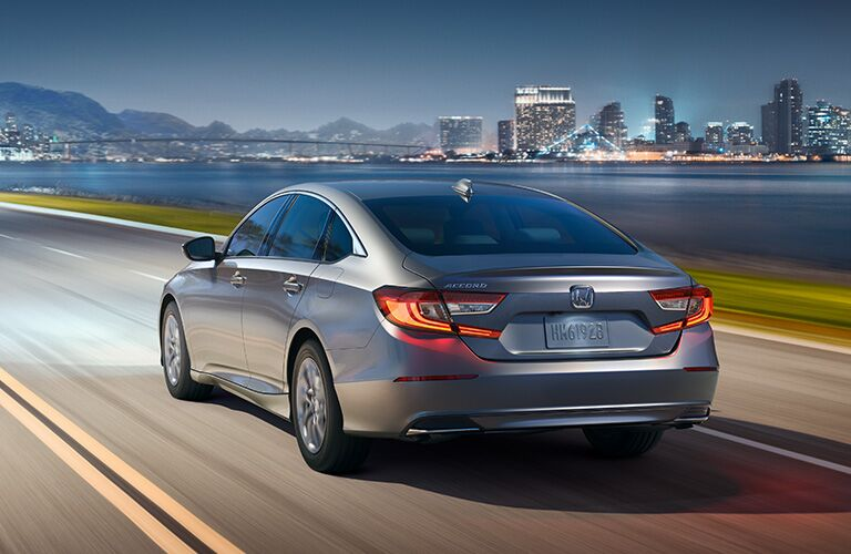 Silver 2019 Honda Accord drives along beside a lake with a city skyline in the distance.