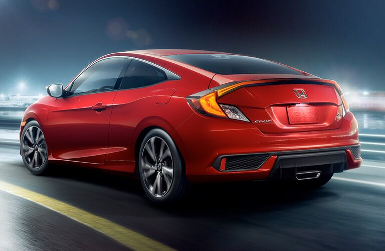 Red 2019 Honda Civic coupe zooms down a highway in the night.