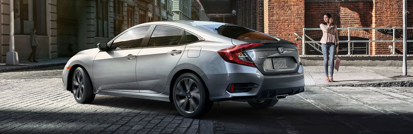 Silver 2019 Honda Civic Sedan turns a corner on a cobblestone street as a woman takes notice.