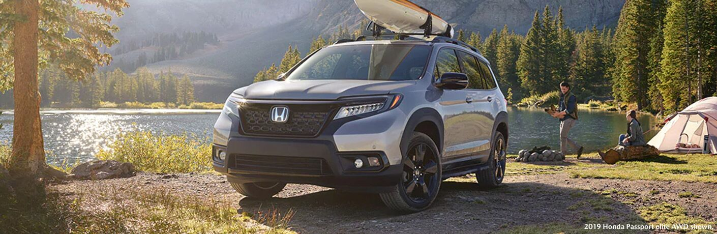 Silver 2019 Honda Passport Next to a River with a Kayak on the Roof with White 2019 Honda Passport Elite AWD Shown Text