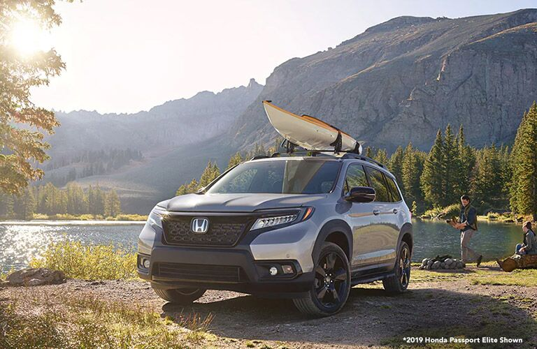 Silver 2019 Honda Passport Next to a River with a Kayak on the Roof and White *2019 Honda Passport Elite Shown Text