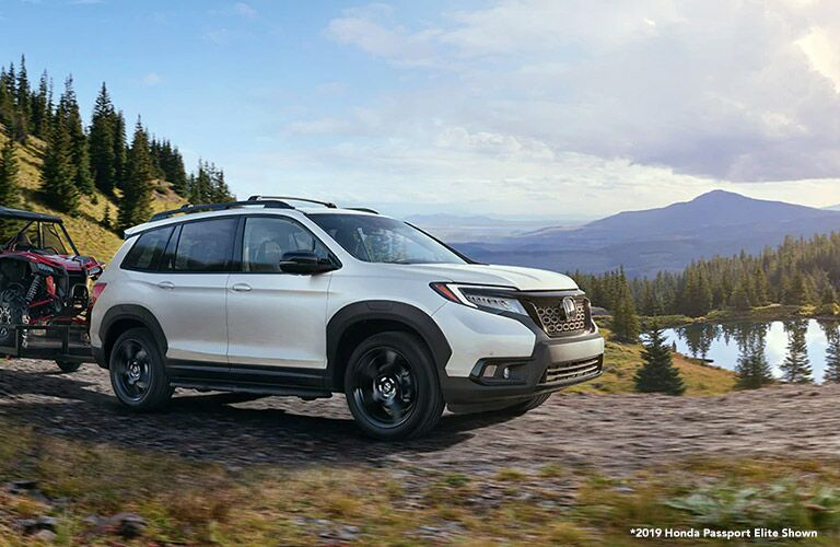 White 2019 Honda Passport Towing ATV on a Trail with White 2019 Honda Passport Elite AWD Shown Text in Bottom Right