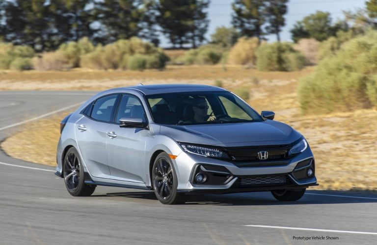 Silver 2020 Honda Civic Hatchback Front Exterior in Desert with Black Prototype Vehicle Shown Text in Lower Right Corner