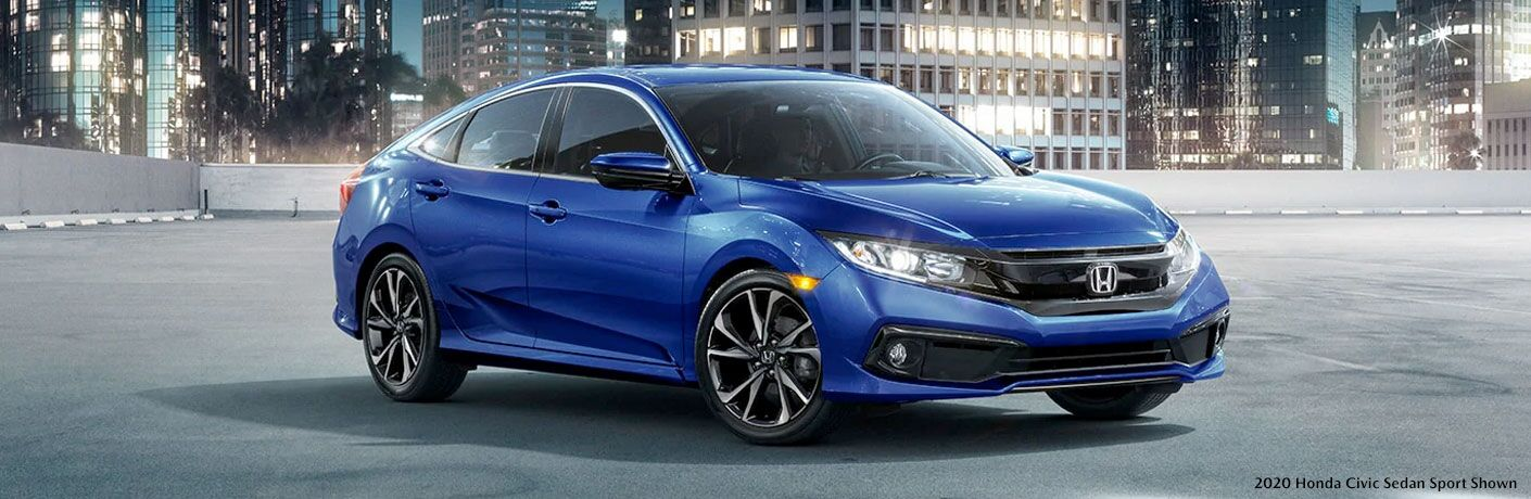 Blue 2020 Honda Civic Sedan in a Parking Lot at Night with Black 2020 Honda Civic Sedan Sport Shown Text in Bottom Right