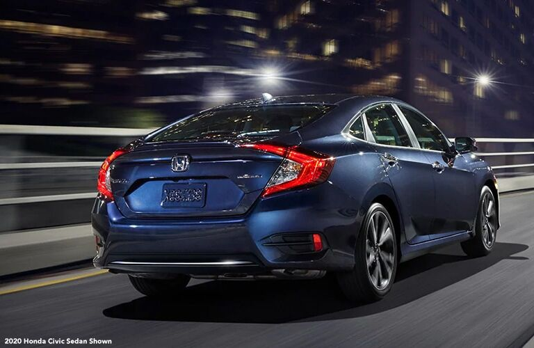 Blue 2020 Honda Civic Sedan Rear Exterior on a Freeway at Night with White 2020 Honda Civic Sedan Shown Text in Lower Left