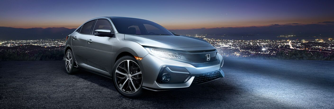 Silver 2020 Honda Civic Hatchback at Night with City Lights in Background