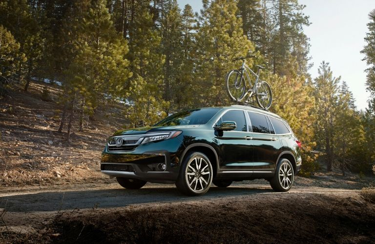 Green 2020 Honda Pilot on a Forest Trail